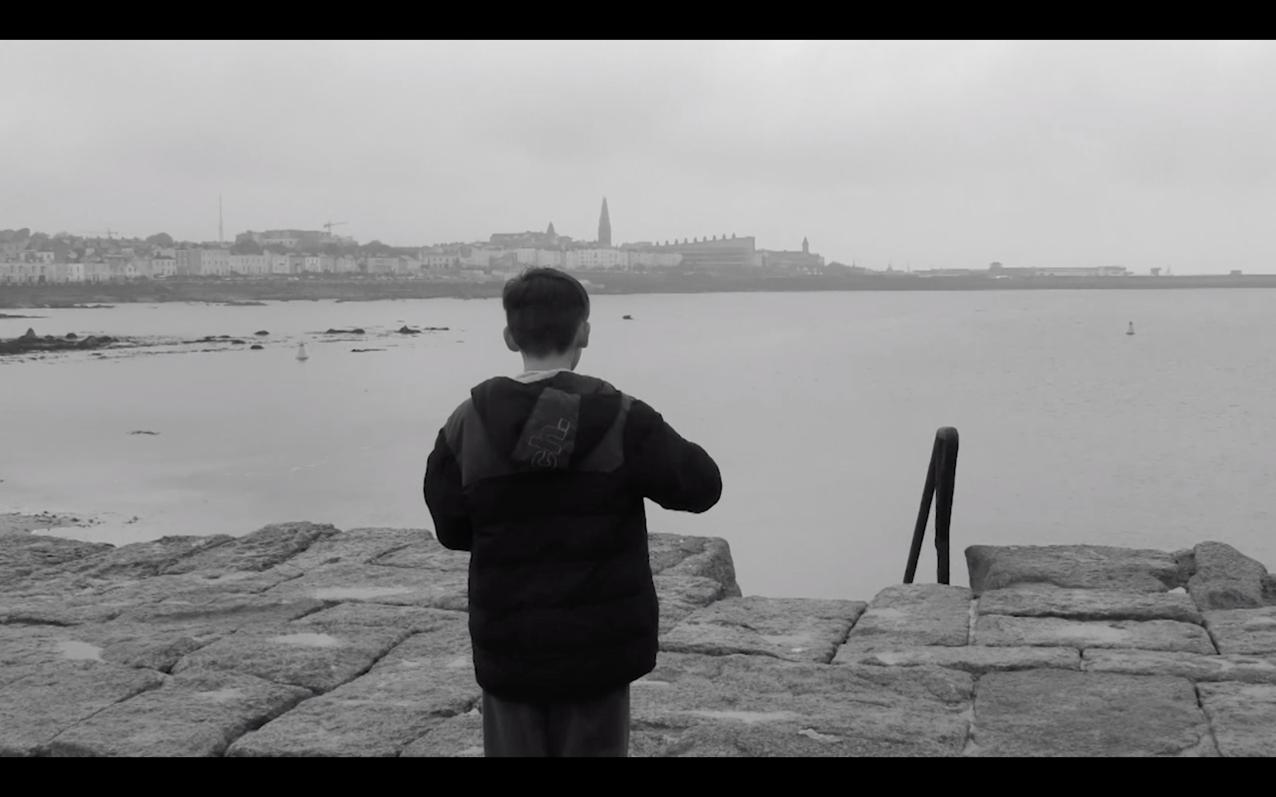 Image of boy with back to camera facing Dún Laoghaire