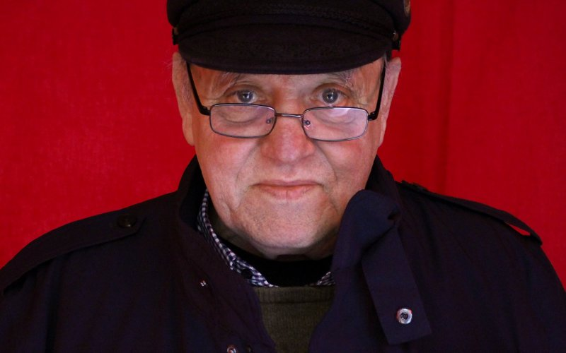Man in black coat, hat and glasses in front of a red curtain