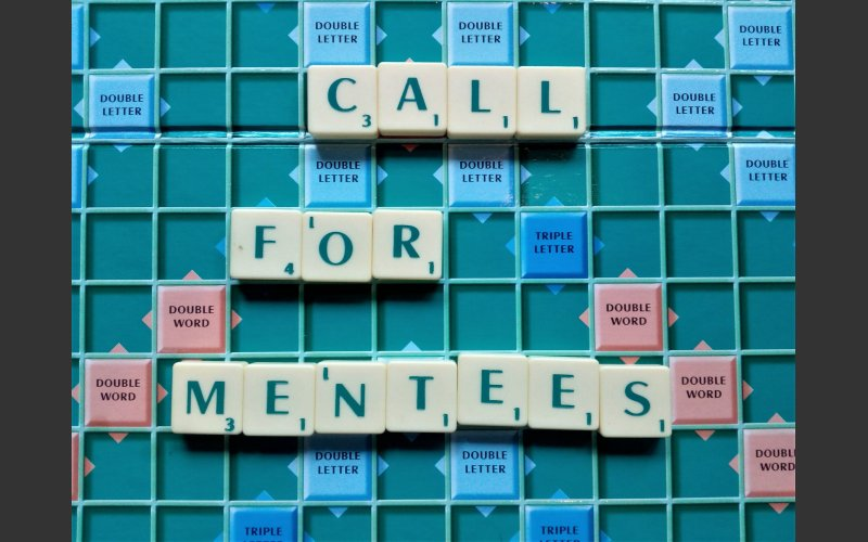 scrabble board and tiles spell out Call for Mentees