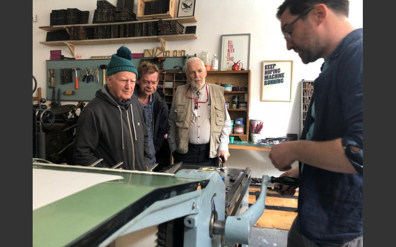 photograph of a group of 3 men from the Men's Shed network visiting Dave Darcy in his letterpress studio