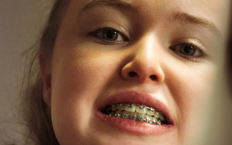 Kelly looking at her new braces in the mirror